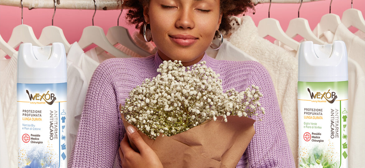 Close up shot of pleased woman holds beautiful bouquet, keeps eyes closed enjoys pleasant smell, poses against clothes hanging in wardrobe on racks, prepares for date. Afro shopaholic with flowers